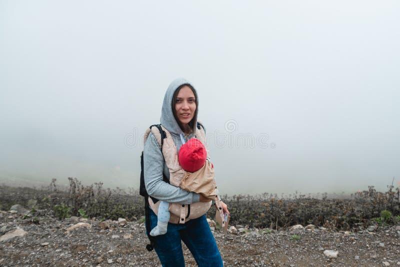 有一个婴孩的年轻母亲背包的 在山的旅行 ? 免版税库存图片