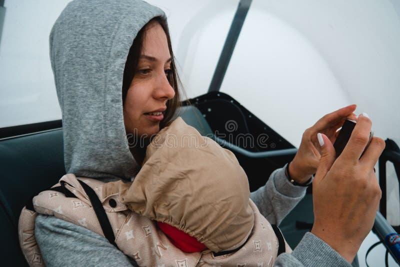 有一个婴孩的年轻母亲背包的 在山的旅行 ? 库存照片