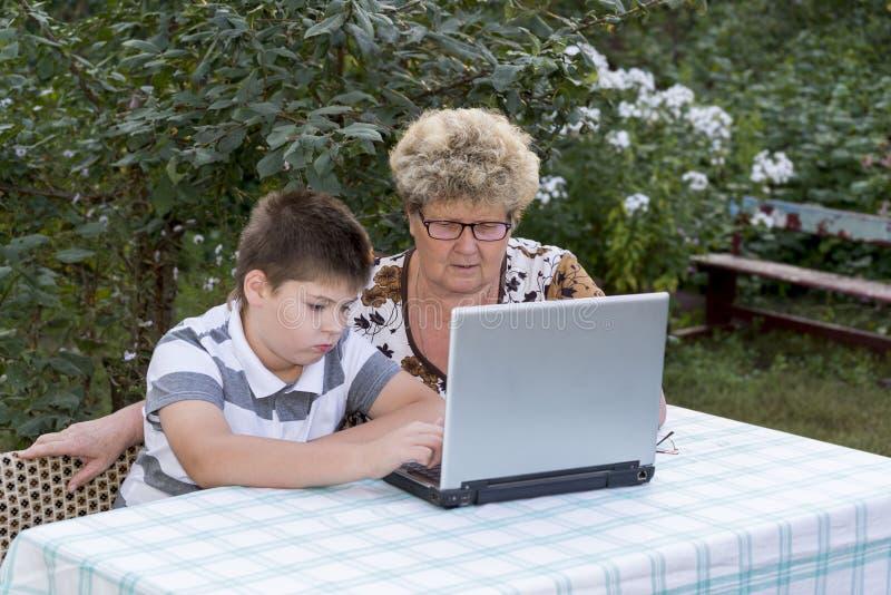 有一个孙子的老婆婆在户外膝上型计算机后 免版税库存照片