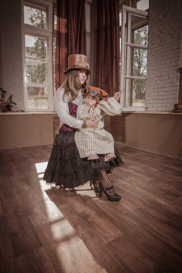 有一个孩子的妇女她的胳膊的,穿戴在衣裳仿照steampunk样式 免版税库存照片