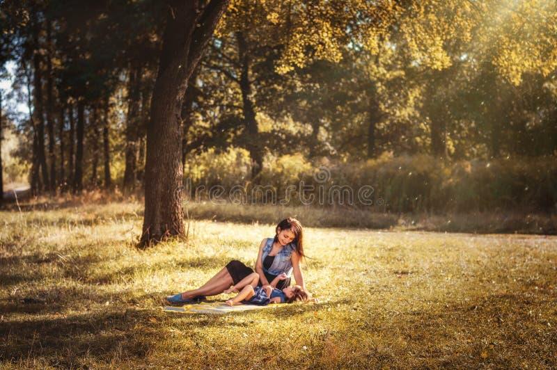 有一个孩子的妈妈步行的在神仙的森林里 免版税库存图片