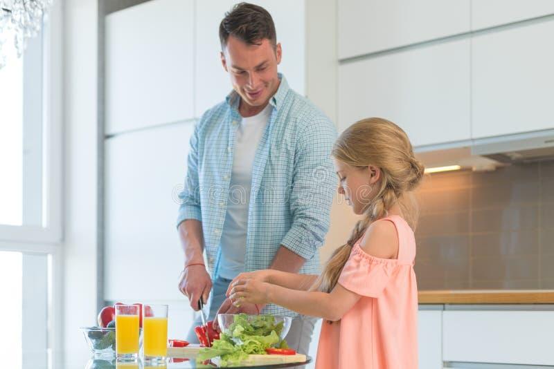 有一个孩子的微笑的家庭在厨房里 库存照片