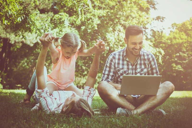 有一个孩子的愉快的家庭本质上 父亲坐草a 免版税图库摄影