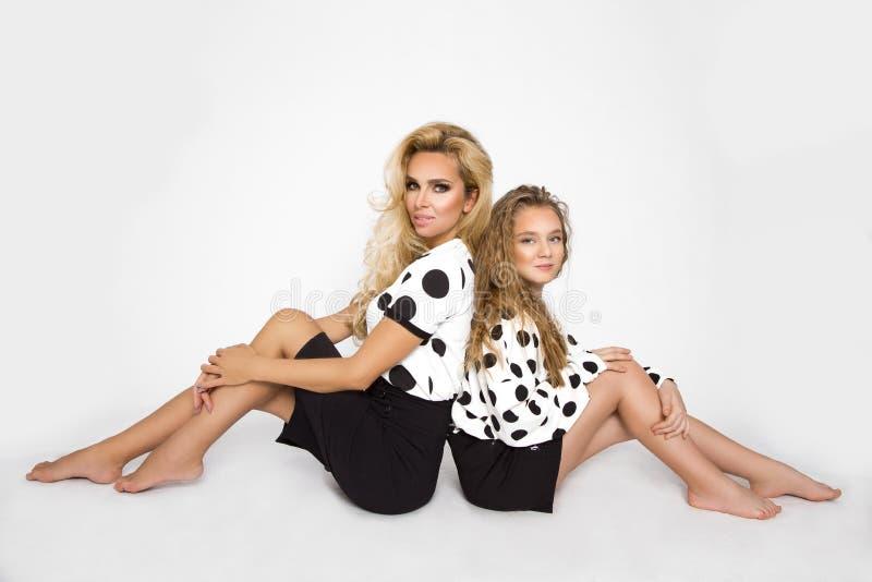 有一个孩子的美丽的妇女短上衣小点的穿衣 妈妈和女儿照相讲席会的 免版税库存图片