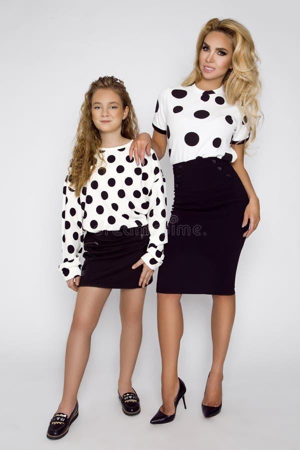 有一个孩子的美丽的妇女短上衣小点的穿衣 妈妈和女儿照相讲席会的 图库摄影