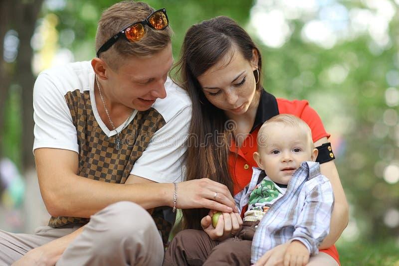 有一个孩子的年轻家庭在夏天公园 库存照片