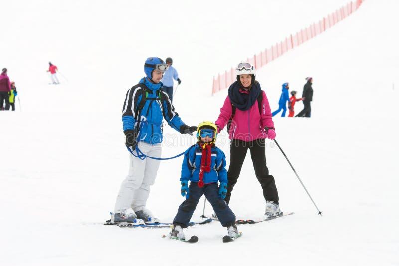 有一个孩子的年轻愉快的家庭,滑雪在山 免版税库存照片