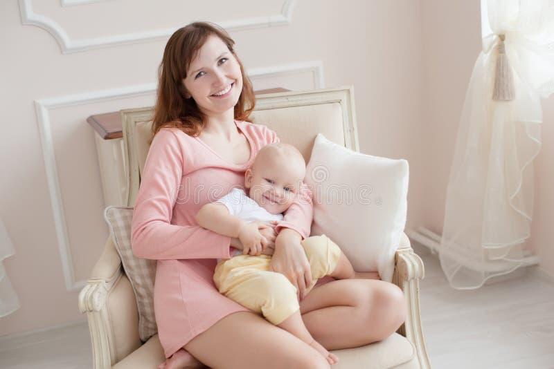 有一个孩子的年轻母亲在卧室早晨 免版税库存图片
