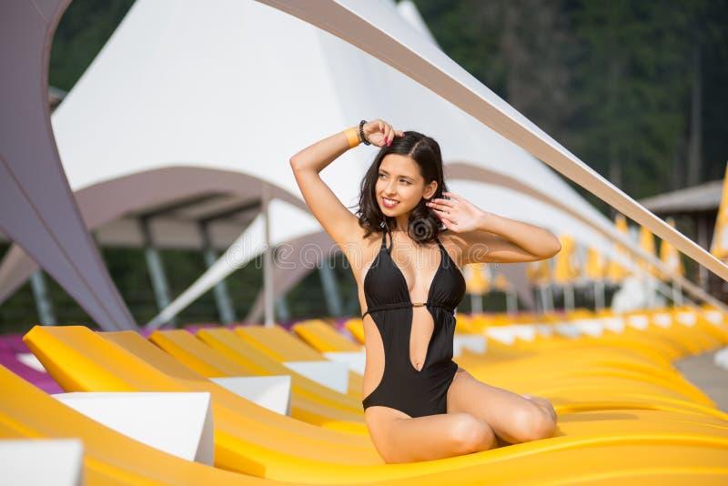 有一个完善的身体的可爱的女性在黑比基尼泳装坐一个紫色懒人用手在豪华旅游胜地 库存图片