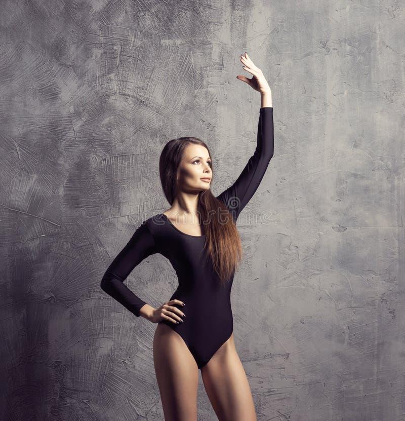 有一个完善的身体的美丽的妇女 摆在和跳舞在泳装的女孩 在具体背景的演播室照片 库存图片