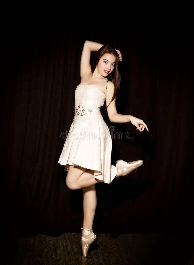 有一个完善的身体的年轻芭蕾舞女演员在黑暗的背景的pointe鞋子跳舞 库存图片