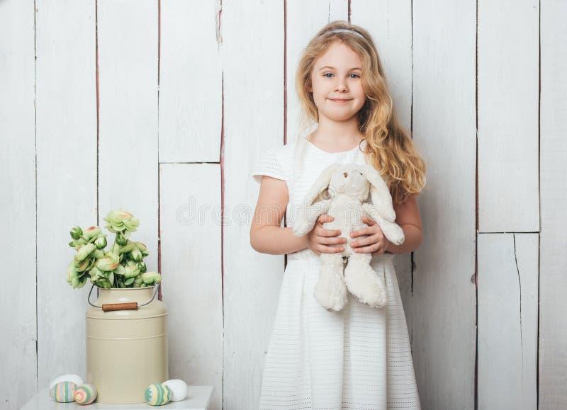 有一个小兔玩具的逗人喜爱的小女孩在白色木背景 库存图片