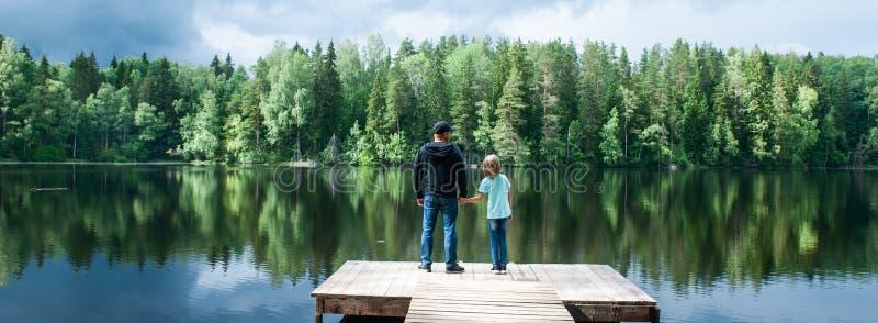 有一个小女儿的父亲在一个美丽的湖的码头站立,父亲打开他的女儿的一个新的世界 免版税库存图片