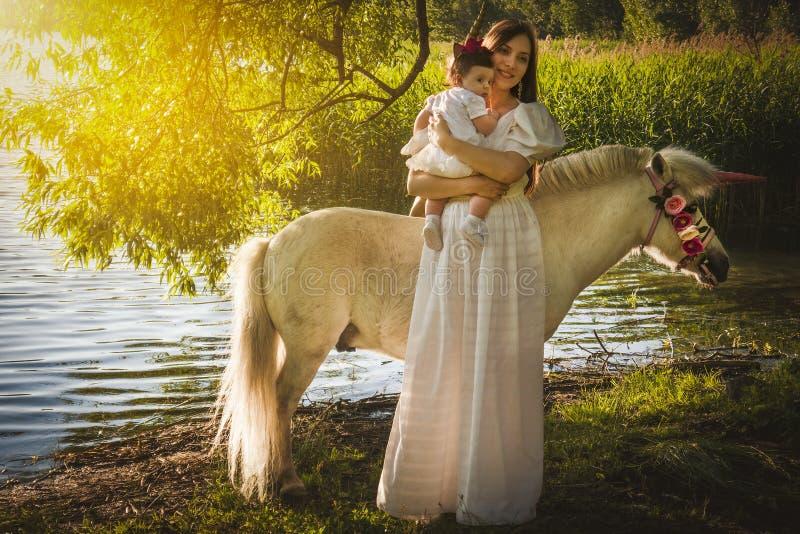 有一个小女儿的美丽的年轻母亲 免版税库存图片