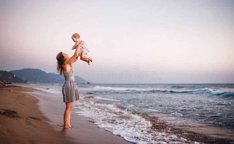 有一个小孩女孩的年轻母亲海滩的在度假夏天休假 r 库存图片