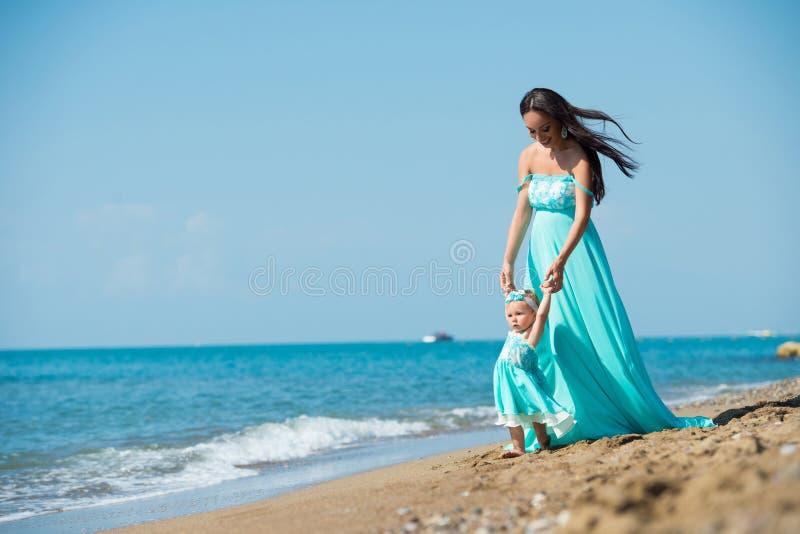 有一个小孩子的母亲由海滩的海走 了解走 免版税库存图片