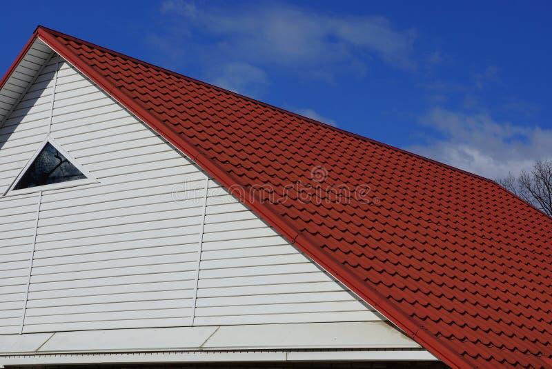 有一个小窗口的白色顶楼在反对天空和云彩的红瓦顶下 库存图片