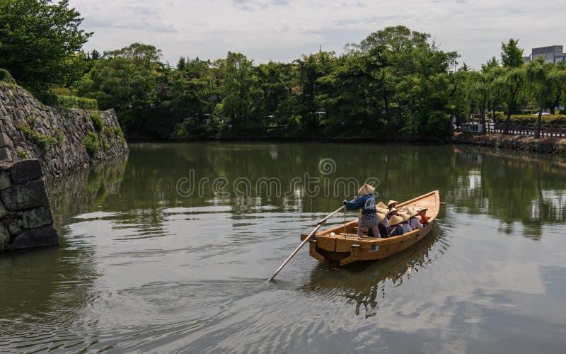有一个小组的传统浮游物游人和指南在姬路城内在护城河  姬路,兵库,日本,亚洲 图库摄影