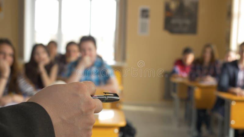 有一个小组的老师高中学生在教室 从解释演讲的老师的手的看法 免版税库存照片