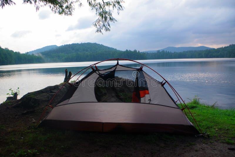 有一个帐篷的原始Bushcraft露营地在水在Adirondack山脉原野 免版税库存图片