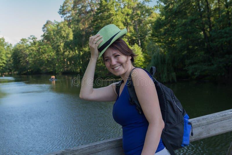 有一个帽子和一个背包的俏丽的妇女在桥梁公园 图库摄影