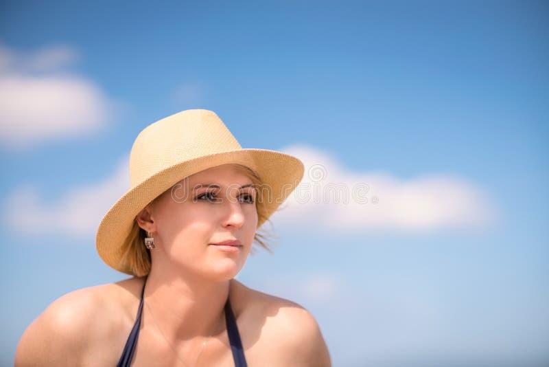有一个帽子的白肤金发的妇女在夏天 库存照片