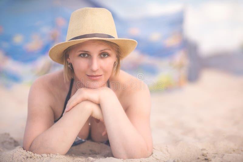 有一个帽子的白肤金发的妇女在夏天 免版税库存图片
