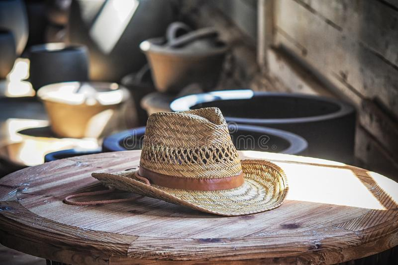 有一个帽边的缎带的白色秸杆牛仔帽在反对黑暗的背景的一张木桌上 图库摄影