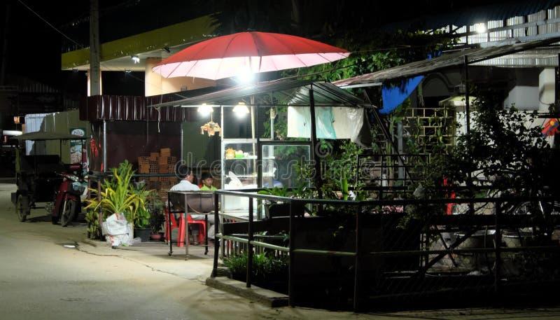 有一个年轻儿子的一个人休息在一个小街道咖啡馆的一把红色伞下 ?? 库存照片
