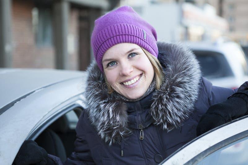 有一个开放车门的愉快的俏丽的妇女 免版税库存图片