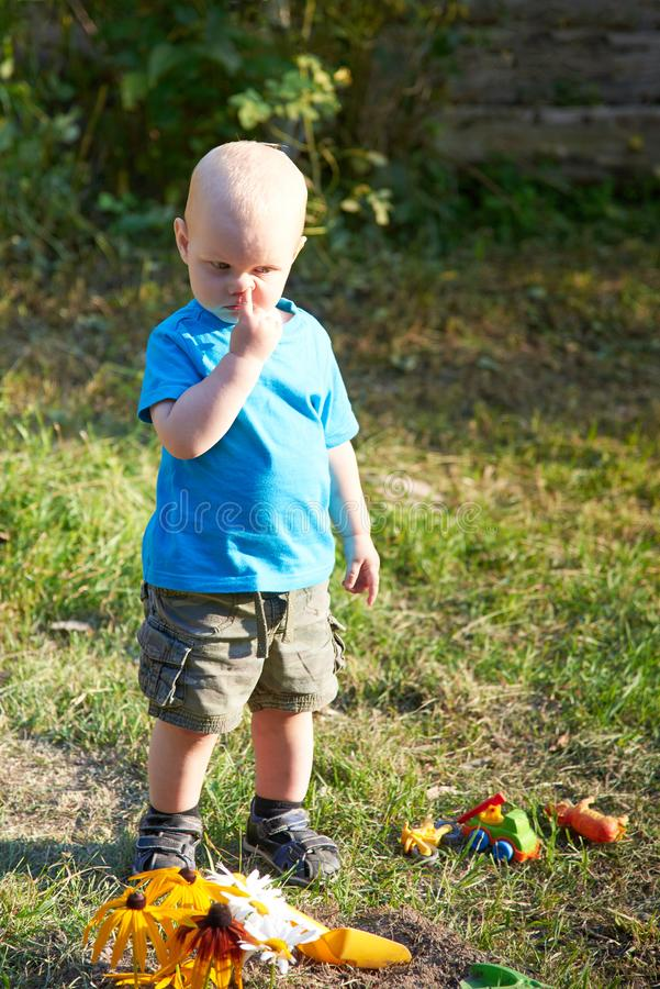有一个手指的一个男孩在他的鼻子在草站立在玩具附近在一个夏日,坏儿童的习性题材  库存照片