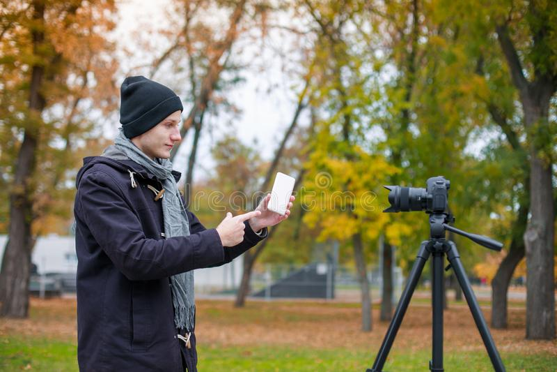 有一个手机的一个孤独的人在他的手上在三脚架的一台照相机被拍摄 户外在公园 库存照片