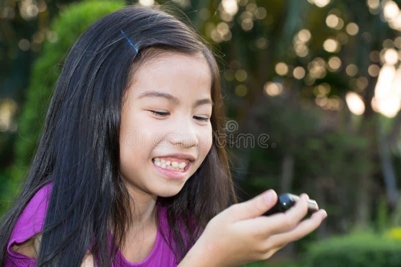 有一个手机的亚裔小女孩 免版税库存照片