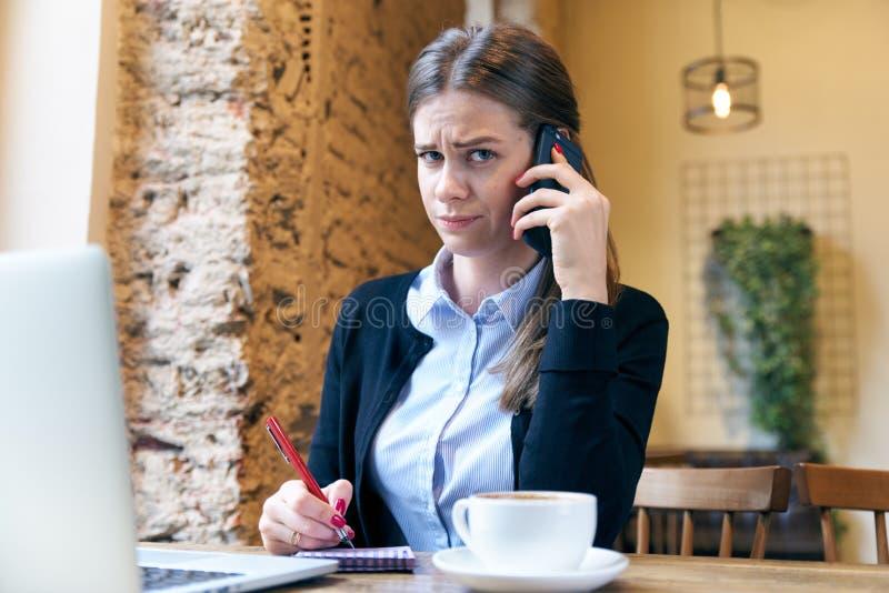 有一个担心的表示的可爱的严肃的妇女谈话在a 免版税库存照片