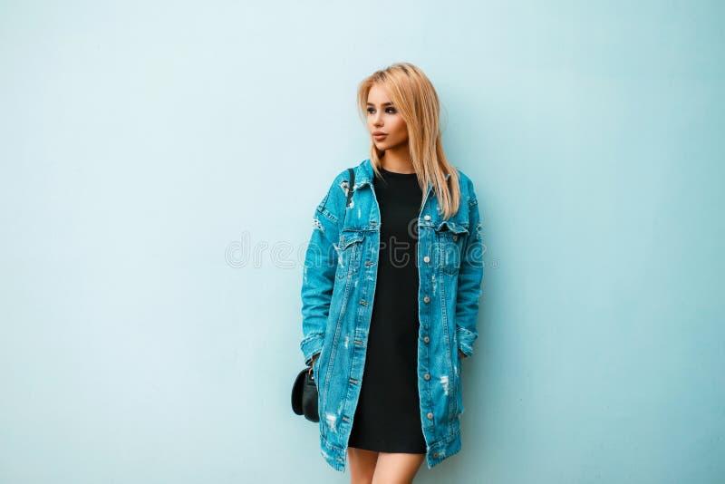 有一个提包的时兴的美丽的少妇在牛仔裤 库存照片