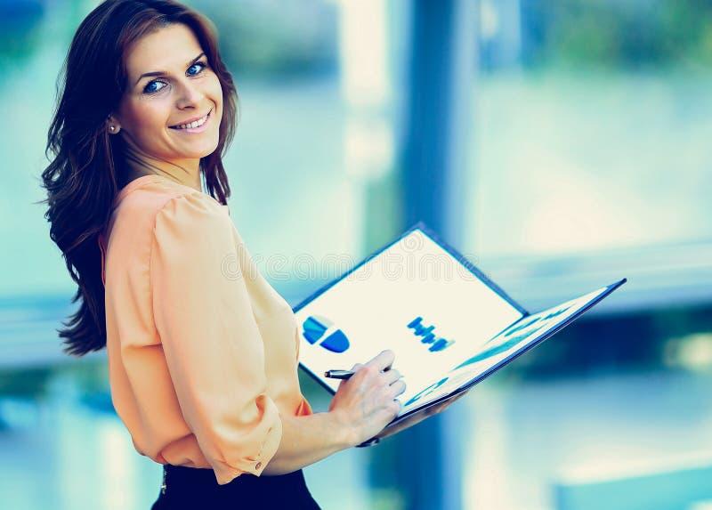 有一个文件夹的可爱的现代年轻女商人在他的手上 免版税库存照片
