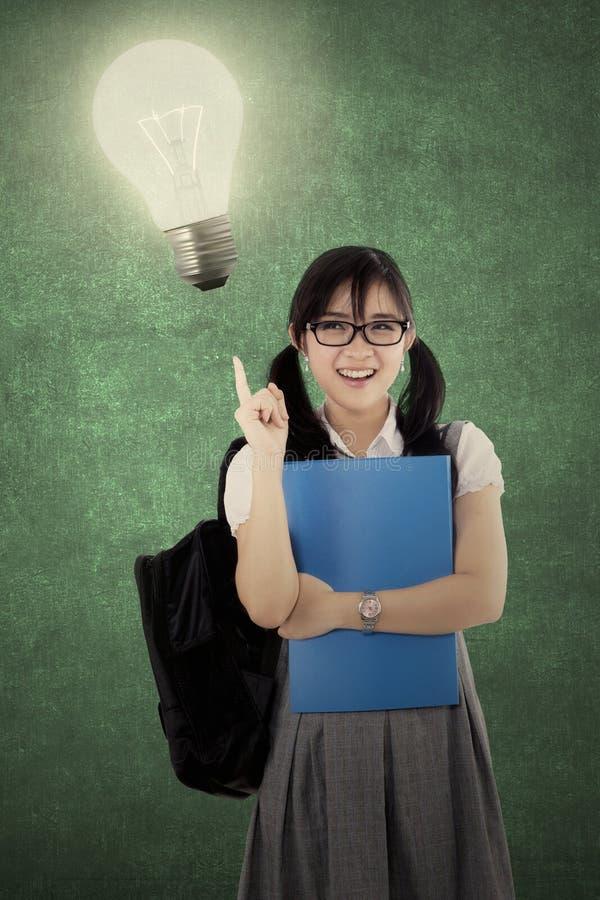 有一个明亮的电灯泡的聪明的高中学生 库存图片