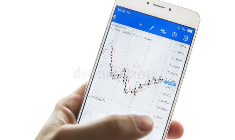 有一个智能手机的被隔绝的商人` s手有证券交易所图的  免版税库存照片