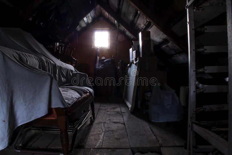 有一个有启发性窗口的黑暗的顶楼 免版税库存照片