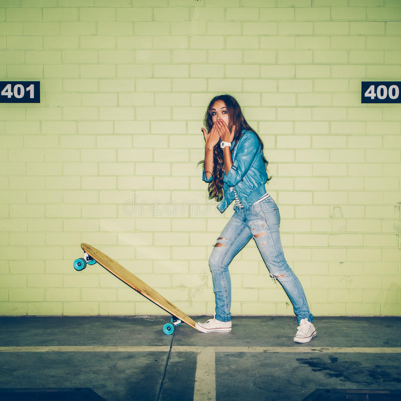 有一个木滑板的美丽的长发妇女在gree附近 免版税库存照片
