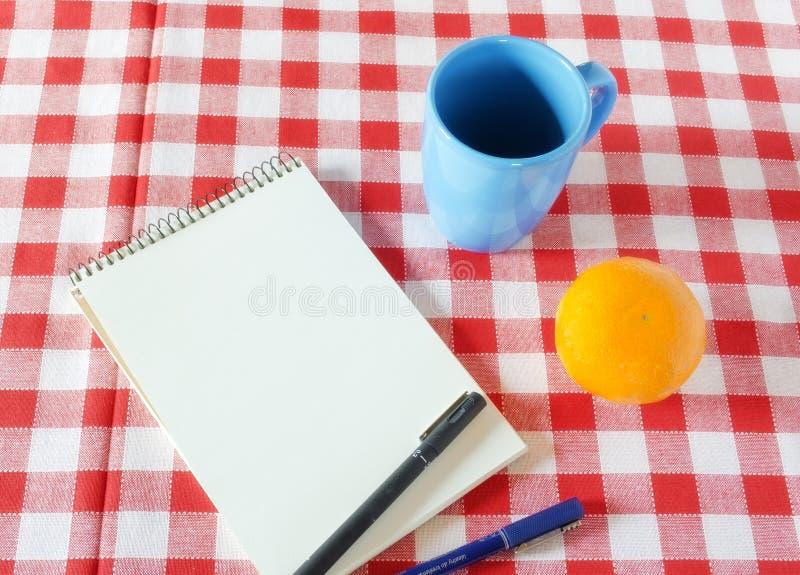 有一个杯子和果子的葡萄酒笔记本在等待的桌上 库存图片
