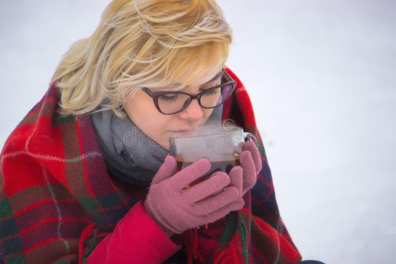 有一个杯子的女孩冬天在公园,阵营炊具 免版税库存照片