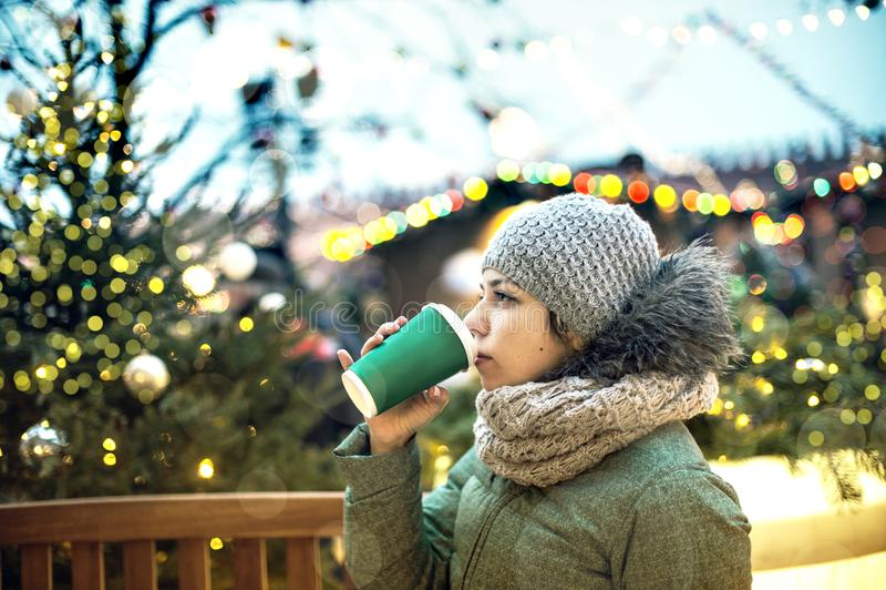 有一个杯子的美丽的女孩热的饮料在圣诞节市场上在莫斯科 库存图片