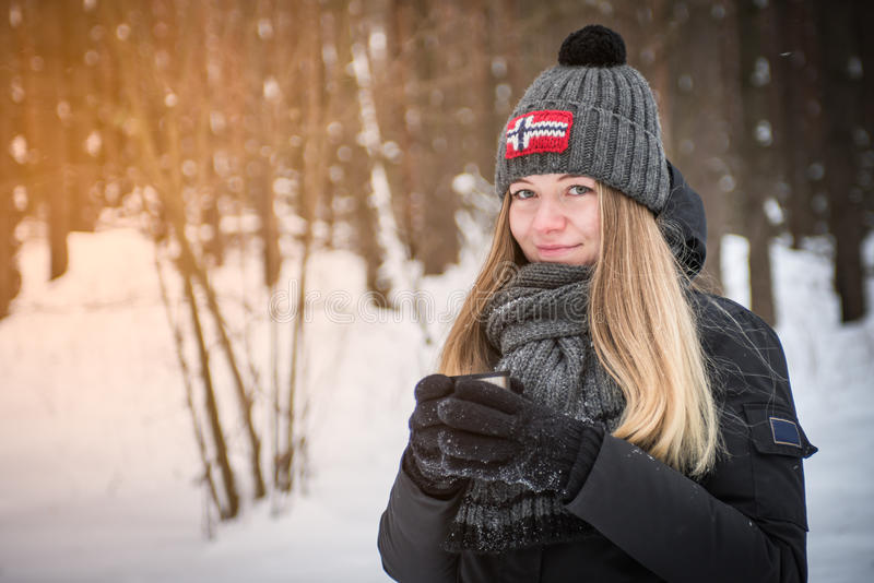 有一个杯子的美丽的愉快的微笑的妇女在街道上的冬天 微笑户外享受女孩热的饮料 库存图片