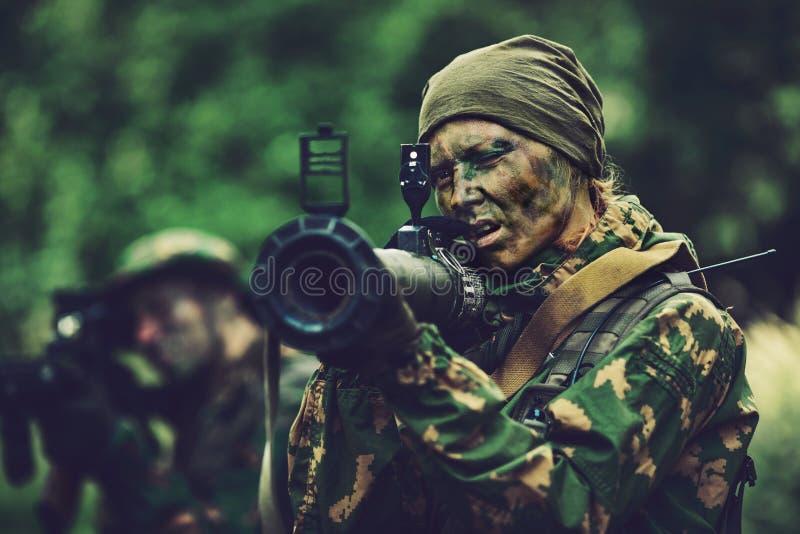 有一个枪榴弹发射器的妇女战士在他的手上在森林里 库存照片
