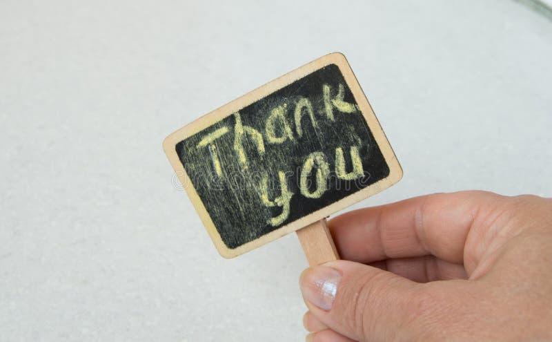 有一个标志的一名妇女在她的有词的手上感谢您 库存图片