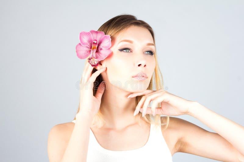 有一个桃红色兰花感人的下巴的妇女有骄傲的神色的 秀丽白肤金发的妇女 免版税库存照片