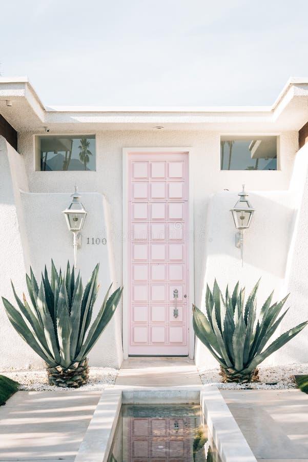 有一个桃红色门的白色房子,在棕榈泉,加利福尼亚 免版税库存照片