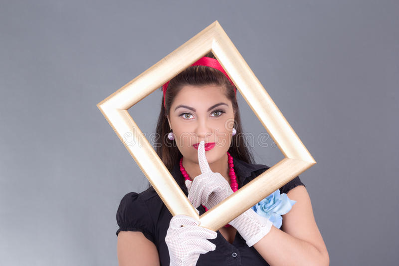 有一个框架的Pinup女孩在她的在嘴唇的面孔和手指附近 库存照片