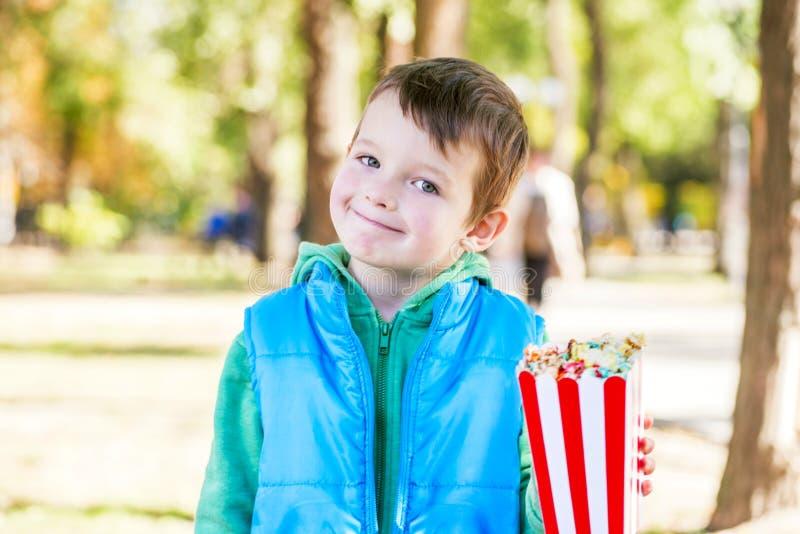 有一个桶的微笑的孩子玉米花在公园在手中走 库存图片